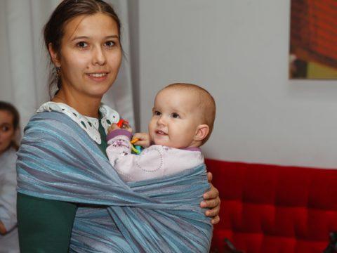 Девушка с ребенком в голубом слинге