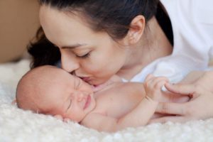 Мать целует младенца